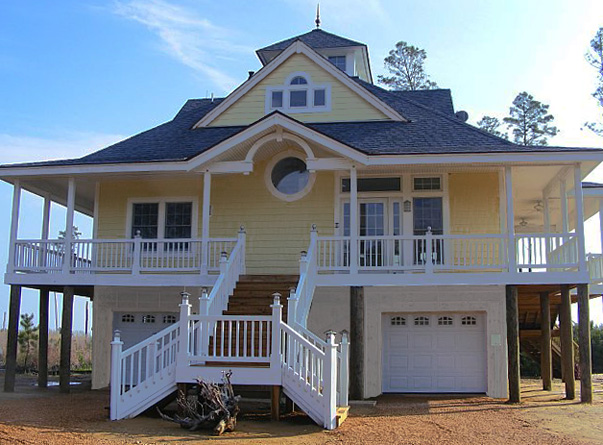 Island cottage piling foundation front entrance garage for Elevated house plans with porches